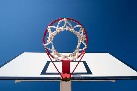 view from down of a Basketball hoop over blue sky background photo
