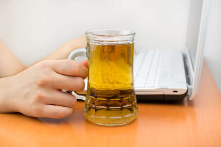 tankard: Woman working at the laptop and drinking a tankard Stock Photo