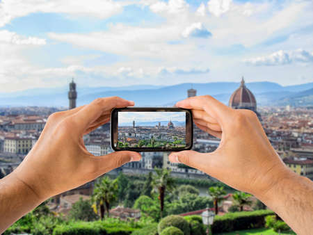 duomo of florence: Tourist takes a picture with his mobile of coliseum in Florence in Italy