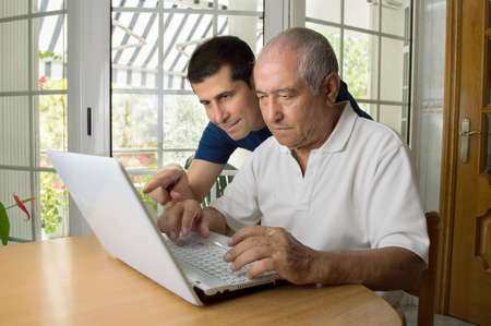 Senior man teaching laptop to his son Imagens