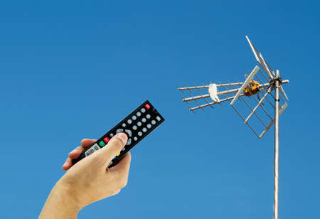 channel surfing: Hand holding a remote to activating a digital antenna tv Stock Photo