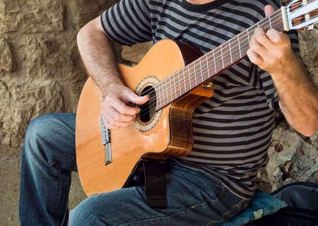 spanish guitar: bohemian performer playing spanish guitar at a street Stock Photo