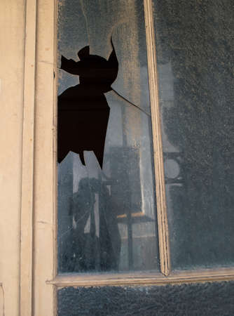 marginalized: close up of broken window of the house of a beggar