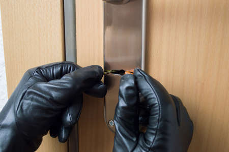 hands gloves of a thief open a security door of a house with a pick lock and tools Stock Photo