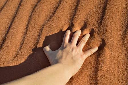 or thirsty: mano sobre la arena del desierto de un hombre sediento y cansado