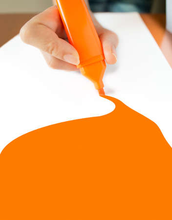 up marker: close up of orange marker drawing on a piece of paper white
