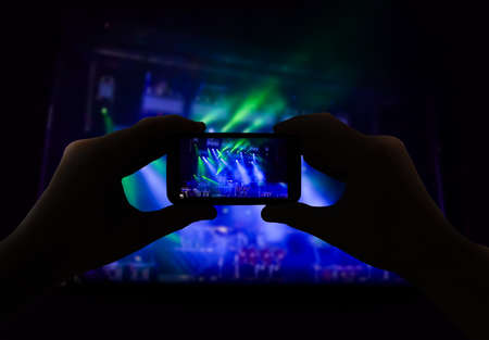 no person: man filming a concert with your mobile phone No person Stock Photo
