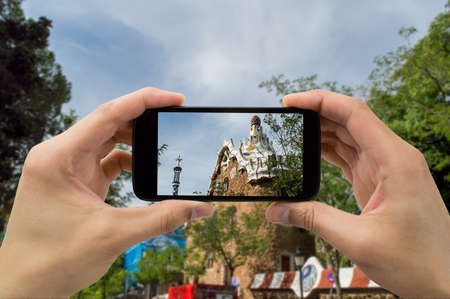 spain: Tourist man taking photo in with smartphone in Park Guell