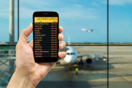departures board: Hand holding mobile smart phone with connect wifi on the airport and see departures board Stock Photo