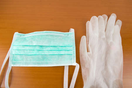 latex gloves: Horizontal view of new hygiene items consisting of latex gloves and mask on a wooden table Stock Photo