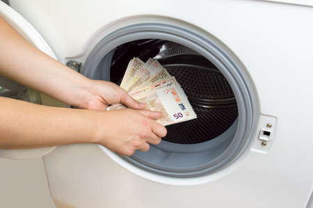 hand putting money into the laundry machine in  concept crime of Money Laundry