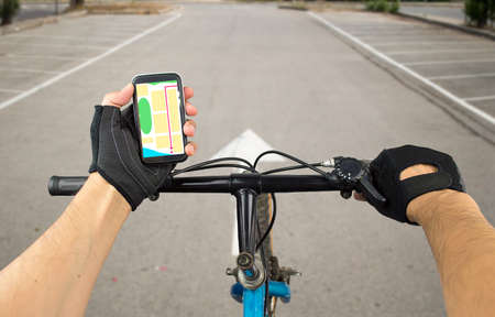 road bike: View a map on the mobile phone on a city bike and search GPS coordinates Stock Photo