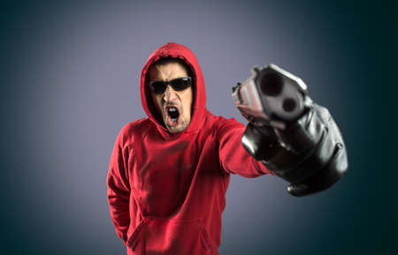 man holding gun: Angry man holding gun against a grey background