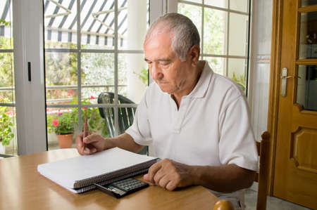 home expenses: Unhappy old man calculating the monthly expenses at home
