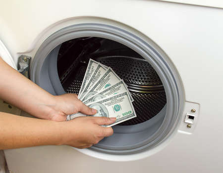 laundry concept: hand putting dollar money into the laundry machine in concept crime of Money Laundry
