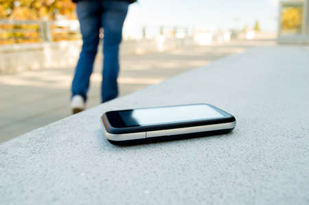 forgot: Someone forgot cell phone on a bench in the park Stock Photo