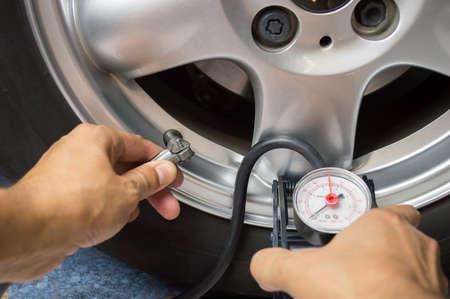 llantas: mano y la rueda de coche añaden presión de aire Foto de archivo