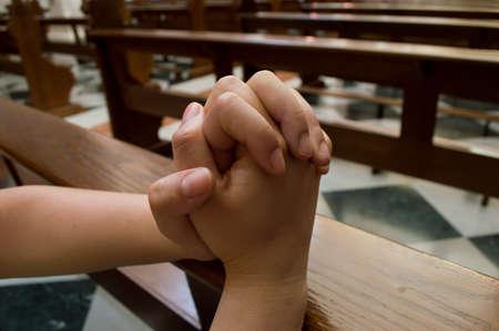 manos unidas: mujer rezando en una iglesia con las manos juntas
