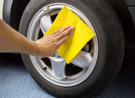 rag wheel: cleaning coated wheels with a yellow cloth at the garage