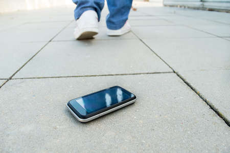 woman who loses the phone and falls in a city Stock Photo