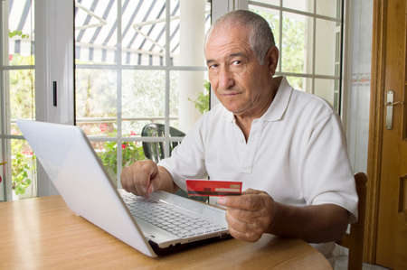 hombres trabajando: anciano compras internet usando su computadora portátil en la sala de Foto de archivo
