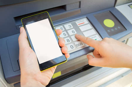 Man typing security PIN code you see on your phone the ATM to withdraw money Reklamní fotografie - 43599764