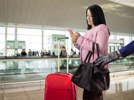 scammer: criminal stealing from the airport terminal to a wandering traveler Stock Photo