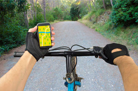 View a map on the mobile phone on a mountain bike and search GPS coordinates Reklamní fotografie - 43599770