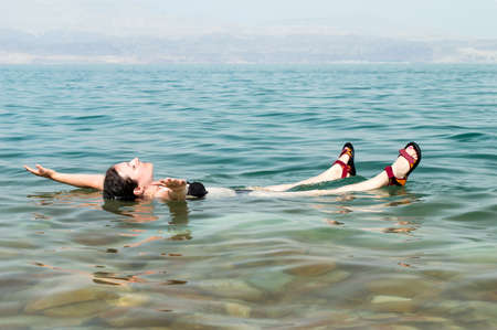 woman floating in a glassy water of dead sea with outstretched arms