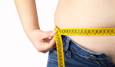 pot belly: obese woman measuring her waist with a measuring tape against a white background Stock Photo