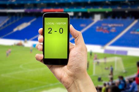 campo di calcio: scommesse l'uomo attraverso il suo telefono intelligente in uno stadio Archivio Fotografico