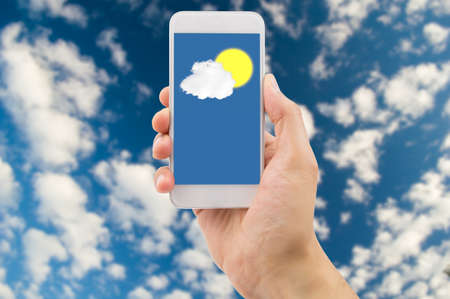 Detail van de hand van raadpleging van de voorspelling weer met de smartphone met wolken en lucht in de achtergrond. Stockfoto