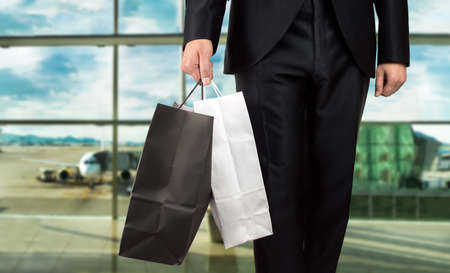 airport: close up of man holding shopping bags walking into airport