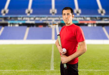 hockey sobre cesped: field hockey player posing wing camera in a stadium