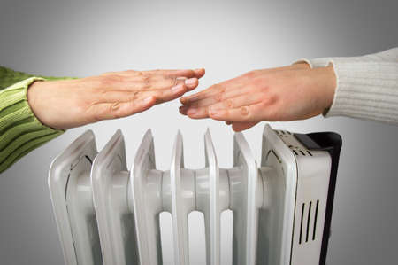 couple warm up hands over electric heater Reklamní fotografie - 43692509