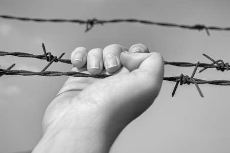 hand taking barbwire in the prison  with sky in background