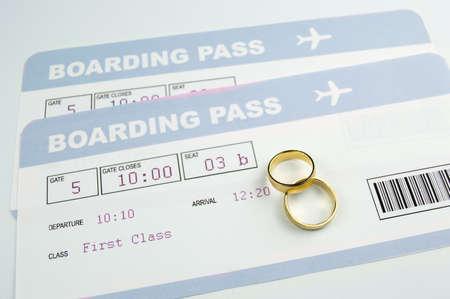 luna de miel: Primer plano de un anillos de boda en una tarjetas de embarque de avi�n de una luna de miel