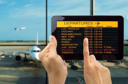 gente aeropuerto: Mano que sostiene la tableta con wifi de conexión en el aeropuerto y ver salidas a bordo Foto de archivo