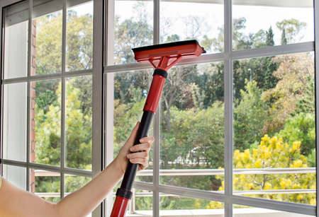 house cleaning: close up of woman cleaning window glass with steam Stock Photo