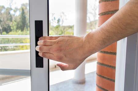 ventana abierta interior: mano de un hombre de cerrar la puerta en invierno