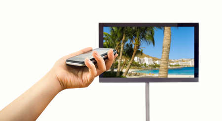 envisioning: closeup of a smartphone connected to a tv and envisioning photos in networking (tv and telephone image from a photo of a beach canaria my portfolio) Stock Photo