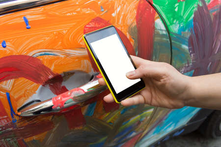 vandalism: man holding the smartphone for calling insurance agency by the vandalism in the car