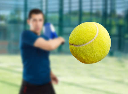male tennis players: close up of ball of paddle tennis player