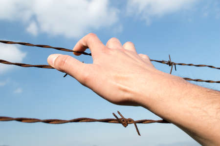 hand taking barbwire in the prison with sky in background Reklamní fotografie