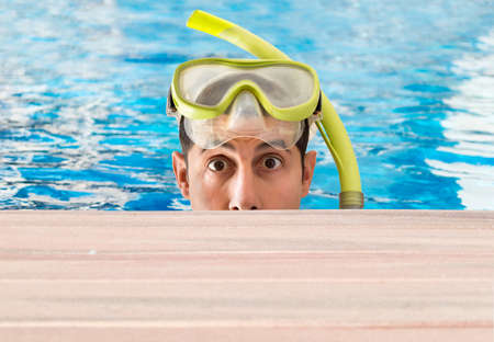 dive trip: man emerging from a pool looking at camera and surprised by what is seen