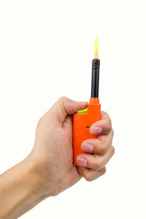 gas lighter: hand pressing the button of orange gas lighter for kitchen with flame