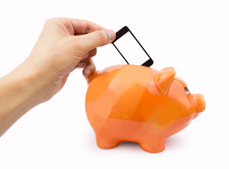 fee: hand putting the cellphone into the piggy bank as concept saving with mobile fee Stock Photo