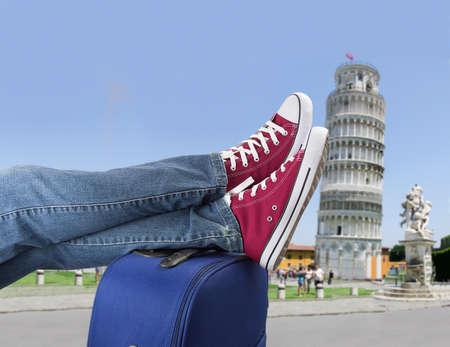 hombre rojo: persona relajada con los pies encima de la maleta a la llegada a Pisa