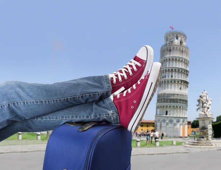 a young man: relaxed person with feet above the suitcase on arrival in Pisa