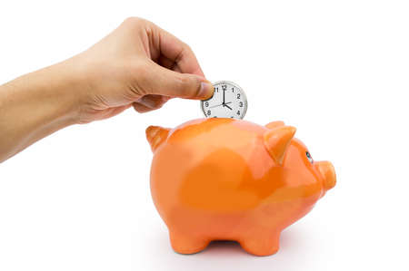 money time: hand holding a clock ticking into the piggy bank Stock Photo